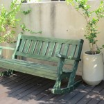 ספסל ירוק מתנדנד. ספסל לגינה, על רצפת עץ. הספסל עשוי מעץ מלא. במידות שונות ובמבחר עשיר של צבעים.